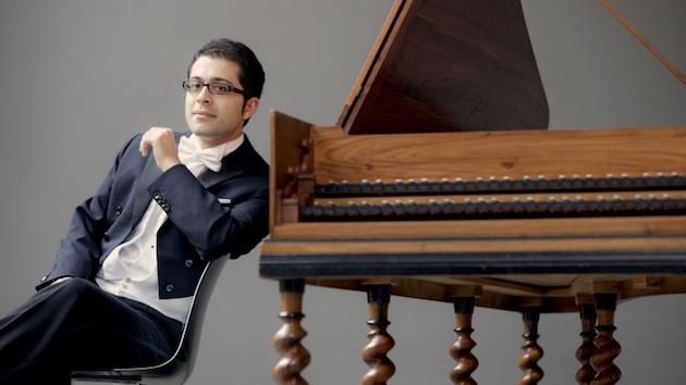 Mahan Esfahani in a tuxedo leans against a harpsichord